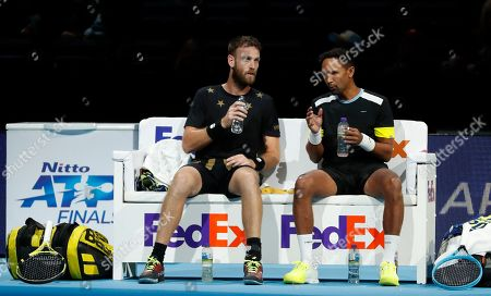 Raven Klaasen of South Africa, right and Michael Venus of New Zealand talks during a change over as they play agaist Lukasz Kubot of Poland and Marcelo Melo of Brazil during their ATP World Tour Finals doubles tennis match at the O2 Arena in London