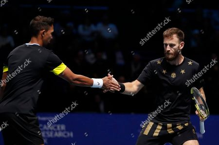 Raven Klaasen of South Africa, left, and Michael Venus of New Zealand tap hands after winning a point against Lukasz Kubot of Poland and Marcelo Melo of Brazil during their ATP World Tour Finals doubles tennis match at the O2 Arena in London