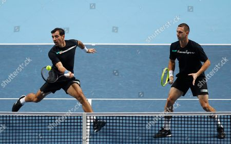 Ivan Dodig of Croatia, left, and Filip Polasek of Slovakia play a return to Rajeev Ram of the United States and Joe Salisbury of Britain during their ATP World Tour Finals doubles tennis match at the O2 Arena in London