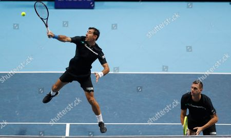 Stock Photo of Ivan Dodig of Croatia, left, and Filip Polasek of Slovakia play a return to Rajeev Ram of the United States and Joe Salisbury of Britain during their ATP World Tour Finals doubles tennis match at the O2 Arena in London