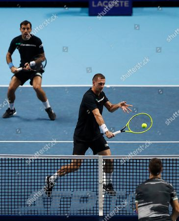 Stock Image of Ivan Dodig of Croatia, left, and Filip Polasek of Slovakia play a return to Rajeev Ram of the United States and Joe Salisbury of Britain during their ATP World Tour Finals doubles tennis match at the O2 Arena in London