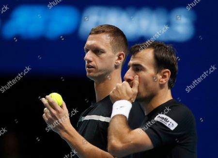 Ivan Dodig of Croatia, right, and Filip Polasek of Slovakia repare to serve to Rajeev Ram of the United States and Joe Salisbury of Britain during their ATP World Tour Finals doubles tennis match at the O2 Arena in London