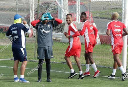 Panama's goalkeeper Jose Calderon looks through his hands as teammates Gabriel Torres, third from right, Jose Luis Rodriguez, second from right, and Azmahar Ariano, far right, jog by during training in Panama City, . Panama will play on Friday a CONCACAF soccer match against Mexico at the Rommel Fernandez stadium