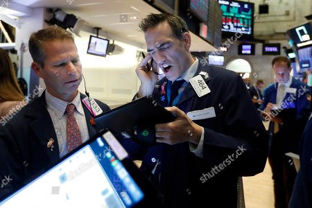 Robert Charmak, Gregory Rowe. Trader Robert Charmak, left, and Gregory Rowe work on the floor of the New York Stock Exchange, . Stocks are opening slightly higher on Wall Street, led by gains in technology and health care companies