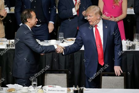 President Donald Trump, right, shakes hands with John Paulson during a meeting of the Economic Club of New York in New York