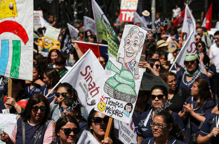 An anti-government demonstrator holds a sign depicting Chile's President Sebastian Pinera during a march near to La Moneda presidential palace in Santiago, Chile, . Students in Chile began protesting nearly a month ago over a subway fare hike. The demonstrations have morphed into a massive protest movement demanding improvements in basic services and benefits, including pensions, health, and education
