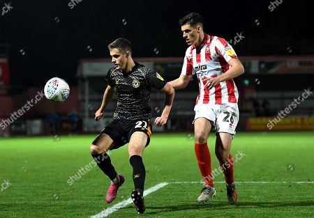 Lewis Collins of Newport County is challenged by Jacob Greaves of Cheltenham Town.