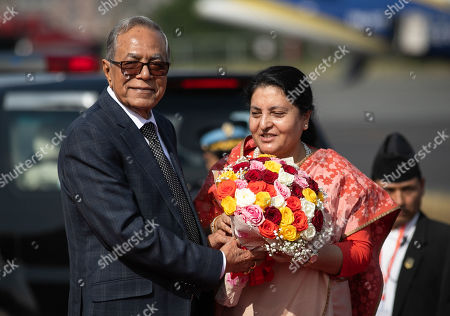 President of Bangladesh, Abdul Hamid (R) receives a bouquet of flowers from Nepal's President, Bidhya Devi Bhandari (L) upon his arrival at Tribhuvan International Airport