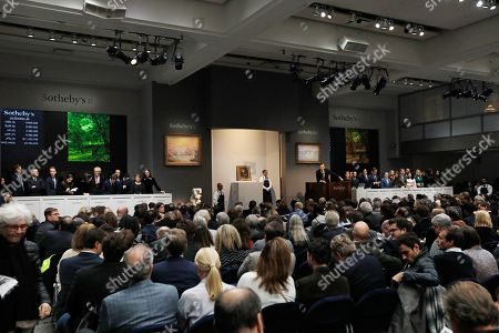 Stock Image of Sotheby's auctioneer Oliver Barker (C-R) takes bids on the 1886 painting by Vincent van Gogh titled 'People Strolling in a Park in Paris' during the Impressionist & Modern Art Evening Sale auction in New York, New York, USA, 12 November 2019.