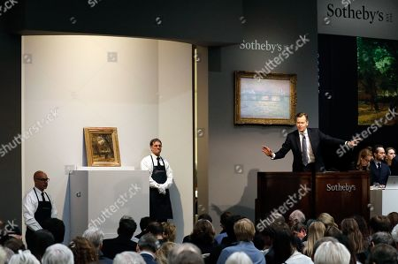 Sotheby's auctioneer Oliver Barker (R) takes bids on the 1886 painting by Vincent van Gogh titled 'People Strolling in a Park in Paris' during the Impressionist & Modern Art Evening Sale auction in New York, New York, USA, 12 November 2019.