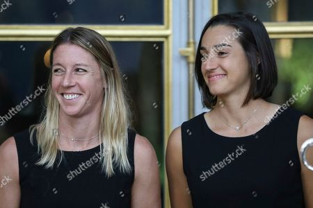 Pauline Parmentier, left, and Caroline Garcia of the French women tennis team pose during a reception at the Elysee presidential palace in Paris, two days after they won the Fed Cup tennis competition