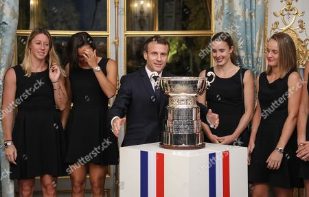 (From L) Pauline Parmentier, Caroline Garcia, Alize Cornet and Fiona Ferro of the French women tennis team abd French President Emmanuel Macron (C) pose during a reception at the Elysee presidential palace in Paris, France, 12 November 2019 (issued 13 November 2019), two days after they won the Fed Cup competition.