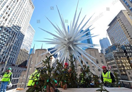 Stock Picture of IMAGE DISTRIBUTED FOR TISHMAN SPEYER - Workers secure the 2019 Swarovski Star to the top of the 77-foot Rockefeller Center Christmas tree, in New York. The iconic star has been reimagined by architect Daniel Libeskind and features 3 million Swarovski crystals on 70 illuminated spikes. The 87th Rockefeller Center Christmas Tree Lighting ceremony will take place on Wednesday, Dec. 4