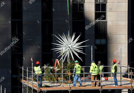 IMAGE DISTRIBUTED FOR TISHMAN SPEYER - Workers secure the 2019 Swarovski Star to the top of the 77-foot Rockefeller Center Christmas tree, in New York. The iconic star has been reimagined by architect Daniel Libeskind and features 3 million Swarovski crystals on 70 illuminated spikes. The 87th Rockefeller Center Christmas Tree Lighting ceremony will take place on Wednesday, Dec. 4