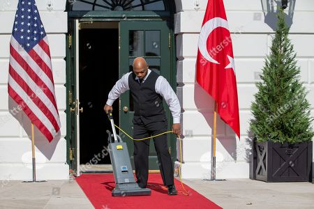 A custodian vacuums the red carpet before US President Donald J. Trump and First Lady Melania Trump greet Turkish President Recep Tayyip Erdogan and his wife, Emine Erdogan at the South Portico of the White House in Washington, DC, USA, 13 November 2019. The visit comes one month after Turkey's invasion into northern Syria against the Kurds and on the first day of public impeachment hearings.
