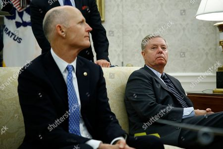 Stock Picture of Sen. Rick Scott, R-Fla., left, and Sen. Lindsey Graham, R-S.C., listen as President Donald Trump and Turkish President Recep Tayyip Erdogan meet in the Oval Office with Republican senators at the White House, in Washington