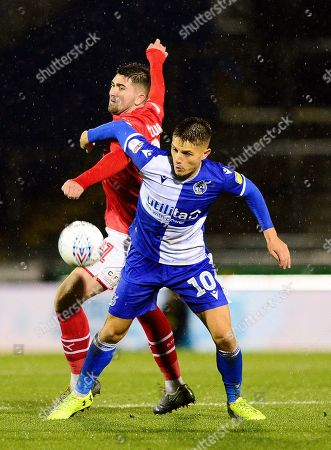 Tom Nichols of Bristol Rovers challenges for the ball with Taylor Curran of Swindon Town