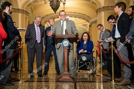 Senator Jon Tester (D-MT) makes a statement following the Democratic Party luncheon on Capitol Hill in Washington, DC, USA, 13 November 2019. Democrats were defending the impeachment proceedings in the House of Representatives and criticized the Trump administration for denying an expansion of benefits for over 80,000 Vietnam War veterans who are suffering from injuries and illnesses that have been connected to the war. Sen. Schumer is flanked by (from left to right) Senate Majority Leader Chuck Schumer, Sen. Sherrod Brown (D-OH), and Sen. Tammy Duckworth (D-IL).