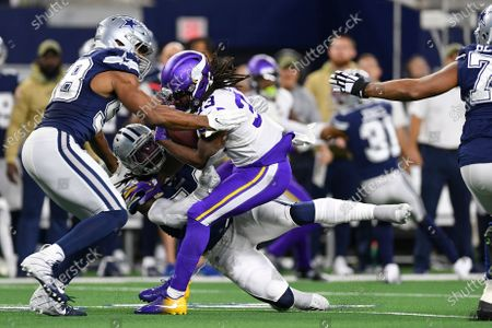 Minnesota Vikings running back Dalvin Cook (33) is tackled by Dallas Cowboys defensive end Robert Quinn (58) and Dallas Cowboys middle linebacker Jaylon Smith (54) during the first half of an NFL football game