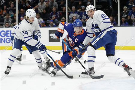 Toronto Maple Leafs' Cody Ceci (83) and Kasperi Kapanen (24) defend New York Islanders' Anders Lee (27) during the second period of an NHL hockey game, in Uniondale, N.Y
