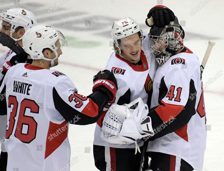 Ottawa Senators goaltender Craig Anderson (41) celebrates with defenseman Thomas Chabot (72) and center Colin White (36) during the third period of the team's NHL hockey game against the New Jersey Devils, in Newark, N.J. The Senators won 4-2