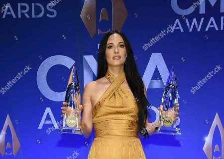 Kasey Musgraves poses in the press room with awards for female vocalist of the year and music video of the year at the 53rd annual CMA Awards at Bridgestone Arena, in Nashville, Tenn