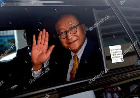 Cambodia's exiled opposition leader Sam Rainsy waves to reporters upon arrival at Soekarno-Hatta International Airport in Tangerang, Indonesia, . Rainsy has arrived in Indonesia to meet some of the country's lawmakers as he considers when and how to make his long-awaited return to his homeland