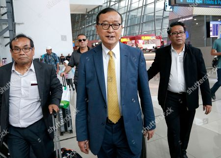 Stock Image of Cambodia's exiled opposition leader Sam Rainsy, center, walks with aides upon arrival at Soekarno-Hatta International Airport in Tangerang, Indonesia, . Rainsy has arrived in Indonesia to meet some of the country's lawmakers as he considers when and how to make his long-awaited return to his homeland