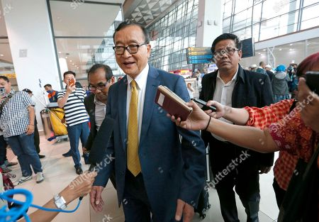 Cambodia's exiled opposition leader Sam Rainsy, center, answers reporters' questions upon arrival at Soekarno-Hatta International Airport in Tangerang, Indonesia, . Rainsy has arrived in Indonesia to meet some of the country's lawmakers as he considers when and how to make his long-awaited return to his homeland