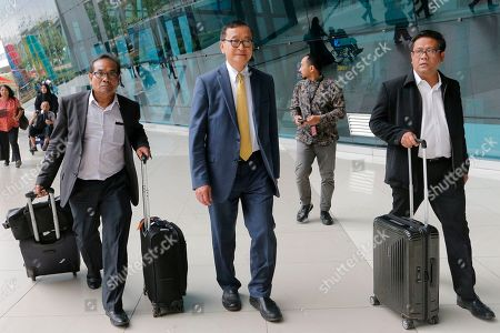 Stock Picture of Cambodia's exiled opposition leader Sam Rainsy, center, walks with aides upon arrival at Soekarno-Hatta International Airport in Tangerang, Indonesia, . Rainsy arrived in Indonesia to meet some of the country's lawmakers as he considers when and how to make his long-awaited return to his homeland