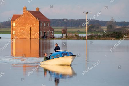 Farmers taking a boat to their farm in Barlings, Lincolnshire which has become an island after being surrounded by flood water on Wednesday afternoon.