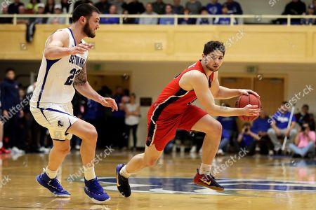 Stony Brook guard Jordan Mckenzie (10) drives to the basket past Seton Hall forward Sandro Mamukelashvili (23) during the first half of an NCAA college basketball game, in South Orange, N.J