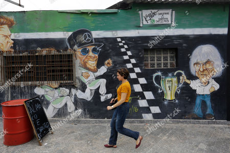 A mural depicts former F1 CEO Bernie Ecclestone, right, next to the world champion driver Lewis Hamilton, center, on the wall of a restaurant located in front of the Interlagos racetrack in Sao Paulo, Brazil. The metropolis' tourism agency says the F1 GP brought revenues of $80 million to Sao Paulo last year