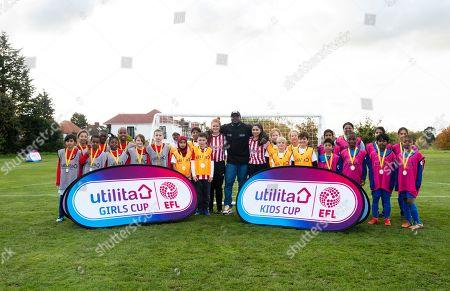 Utilita Kids & Girls Cup  Adebayo Akinfenwa poses with the children plus Charlotte Tanner and Nicole Goolab