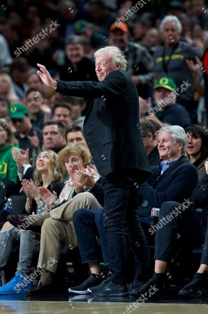 Stock Picture of Nike co-founder Phil Knight waves to the crowd during the second half of an NCAA college basketball game between Oregon and Memphis in Portland, Ore., . Oregon won 82-74