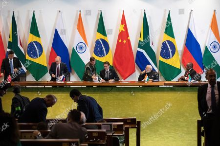 China's President Xi Jinping, left, Russia's President Vladimir Putin, second from left, Brazil's President Jair Bolsonaro, center, India's Prime Minister Narendra Modi, second from right, and South Africa's President Cyril Ramaphosa leave after a meeting with members of the Business Council and management of the New Development Bank during the BRICS emerging economies at the Itamaraty palace in Brasilia, Brazil