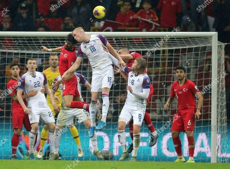 Mahmut Tekdemir, Hordur Magnusson. Turkey's Mahmut Tekdemir, left center, jumps for the ball with Iceland's Hordur Magnusson, right center, during the Euro 2020 Group H qualifying soccer match between Turkey and Iceland in Istanbul
