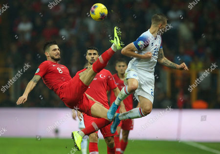 Okay Yokuslu, Arnor Ingvi Traustason. Turkey's Okay Yokuslu, left, challenges for the ball with Iceland's Arnor Ingvi Traustason during the Euro 2020 Group H qualifying soccer match between Turkey and Iceland in Istanbul