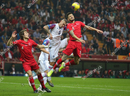 Okay Yokuslu, Ragnar Sigurdsson, Caglar Soyuncu. Turkey's Okay Yokuslu, right, jumps for the ball with Iceland's Ragnar Sigurdsson, center, during the Euro 2020 Group H qualifying soccer match between Turkey and Iceland in Istanbul