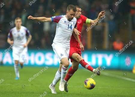 Burak Yilmaz, Kari Arnason. Turkey's Burak Yilmaz, right, fights for the ball with Iceland's Kari Arnason, left, during the Euro 2020 Group H qualifying soccer match between Turkey and Iceland in Istanbul