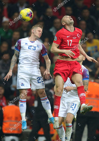 Burak Yilmaz, Ari Skulason. Turkey's Burak Yilmaz, right, jumps for the ball with Iceland's Ari Skulason, left, during the Euro 2020 Group H qualifying soccer match between Turkey and Iceland in Istanbul