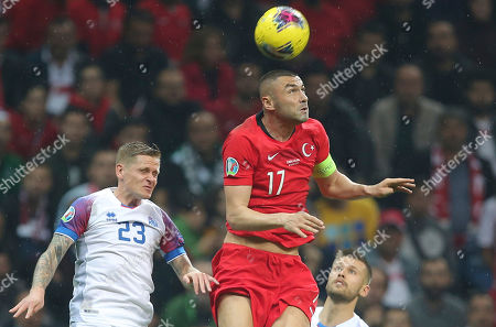 Burak Yilmaz, Ari Skulason. Turkey's Burak Yilmaz, right, jumps for the ball with Iceland's Ari Skulason during the Euro 2020 Group H qualifying soccer match between Turkey and Iceland in Istanbul