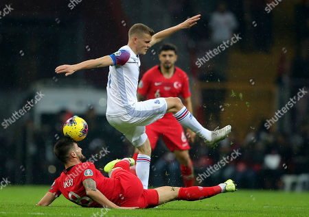 Okay Yokuslu, Alfred Finnbogason. Turkey's Okay Yokuslu, on the ground, fights for the ball with Iceland's Alfred Finnbogason during the Euro 2020 Group H qualifying soccer match between Turkey and Iceland in Istanbul