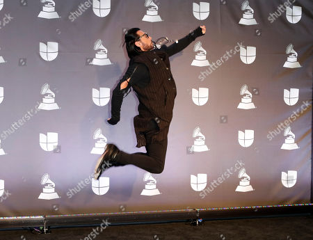 Stock Picture of Performer Beto Cuevas leaps for a pose in the press room during the 20th annual Latin Grammy Awards ceremony at the MGM Grand Garden Arena in Las Vegas, Nevada, USA, 14 November 2019. The Latin Grammys recognize artistic and/or technical achievement, not sales figures or chart positions, and the winners are determined by the votes of their peers - the qualified voting members of the Latin Recording Academy.