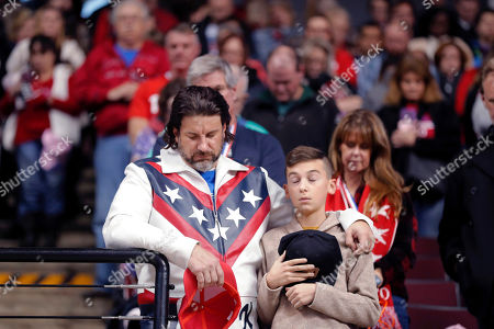 A man dressed as Evel Knievel prays with a boy prays during the invocation at the start of a campaign rally for President Donald Trump in Bossier City, La