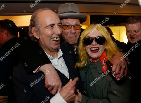 The Clash lead guitarist Mick Jones, left, smiles as he gets hugs from Big Audio Dynamite bass player Gary Stonadge, middle, and fashion designer Pam Hogg, right, at the Museum of London reception for the opening of the 40th Anniversary of The Clash London Calling album exhibition, in London