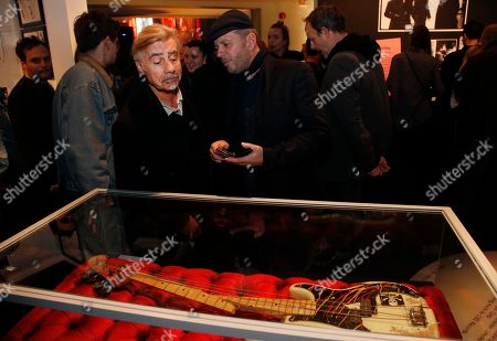 Stock Photo of Former Sex Pistols bass player Glen Matlock, left, takes a look at the smashed bass guitar destroyed by The Clash bass player Paul Simonon that created the iconic album cover of London Calling at the Museum of London reception for the opening of the 40th Anniversary of The Clash London Calling album exhibition, in London
