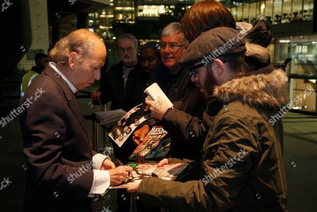 Stock Photo of Mick Jones, left, The Clash lead guitarist and part of the Mick Jones and Joe Strummer writing duo, signs autographs for fans at the Museum of London reception for the opening of the 40th Anniversary of The Clash London Calling album exhibition, in London