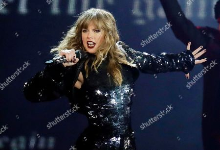 """Taylor Swift performing during her """"Reputation Stadium Tour"""" opener in Glendale, Ariz. Swift says she may not be performing at the American Music Awards because the men who own her old recordings won't allow her to play her songs. Swift said on Instagram Thursday that she planned to play a medley of her hits when she's named Artist of the Decade at the American Music Awards on Nov. 24. But Swift says the men who own the music, Scooter Braun and Scott Borchetta, are calling the performance an illegal re-recording"""