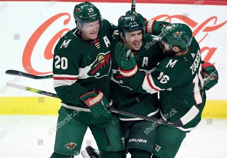 Minnesota Wild's Ryan Suter (20) and Jason Zucker (16) congratulate left wing Zach Parise (11) on his goal against the Arizona Coyotes during the third period of an NHL hockey game, in St. Paul, Minn. The Wild won 3-2